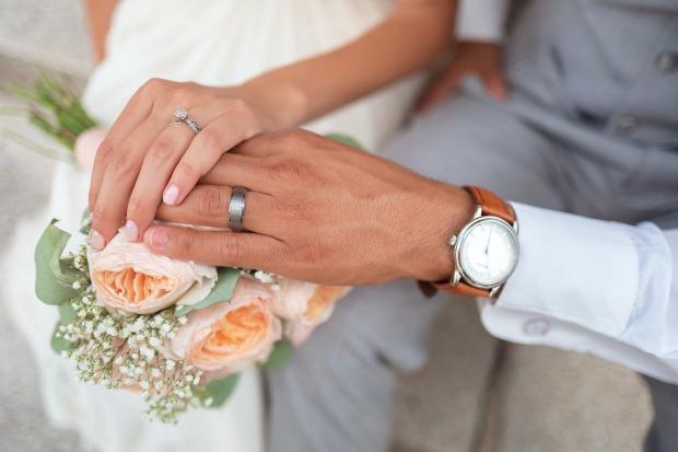 руки молодоженов лежат на красивом свадебном букете