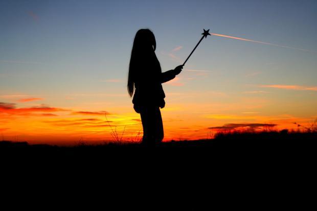 девушка с волшебной палочкой на фоне заката