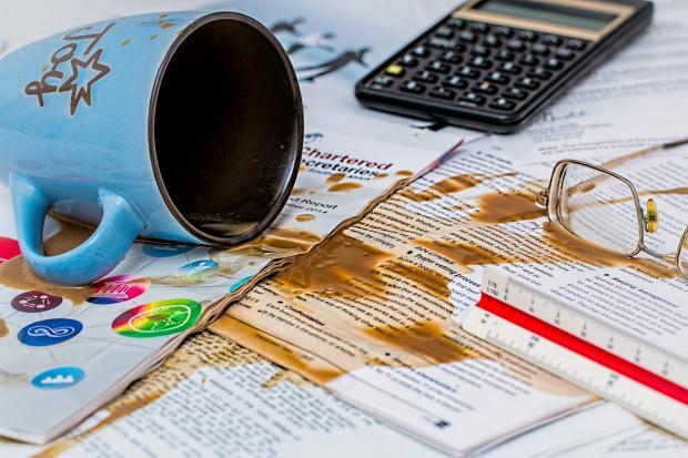 опрокинутая на бумаги чашка с кофе