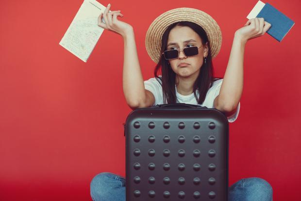 Молодая девушка в шляпе сидит на стуле