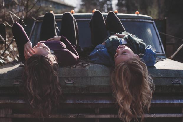 две девушки смеются на машине