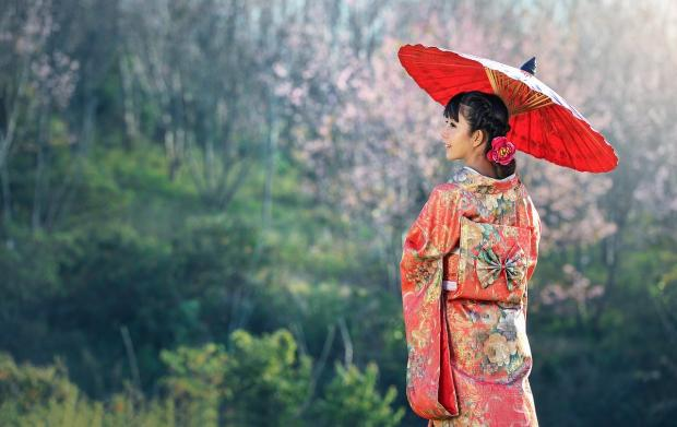 молодая японка в национальной одежде с зонтиком на фоне природы