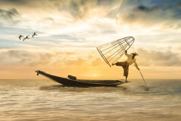 японский рыбак на лодочке в океане