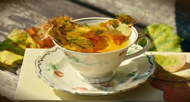 красивая чашка на блюдце с чаем с плавающими листьями