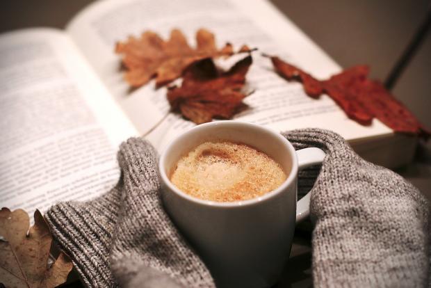 кофе в чашке и книга с листьями