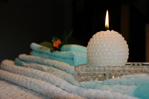 белая круглая свеча стоит на стопке полотенец
