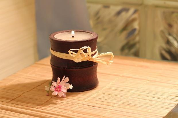 свеча в керамическом подсвечнике на соломенной циновке