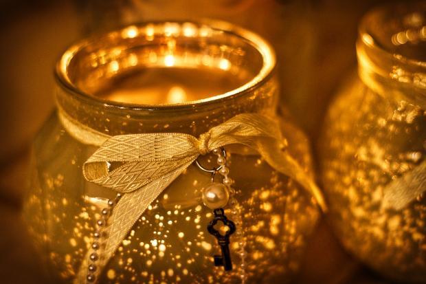 горящие свечи в декоративных сосудах золотистого цвета