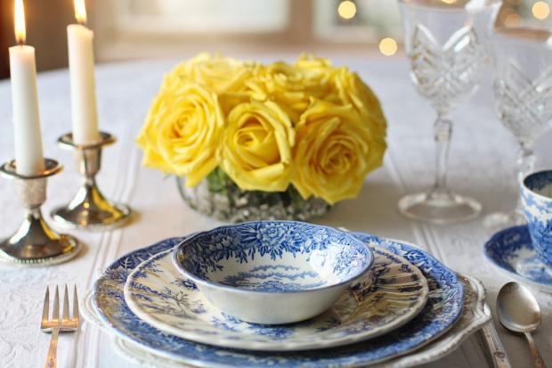праздничный стол с белыми свечами и желтыми цветами