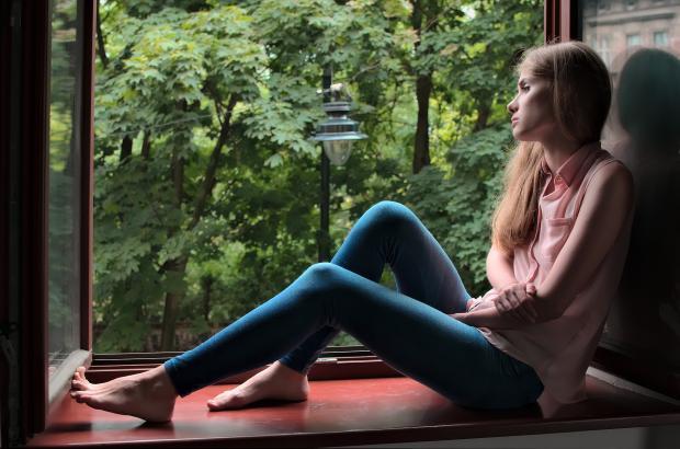 девушка сидит на подоконнике и смотрит в лес