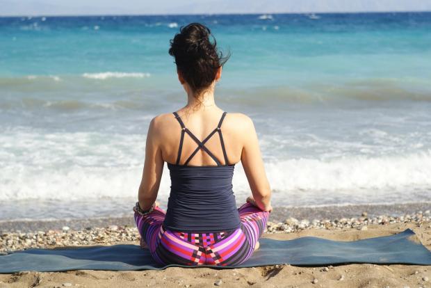 девушка медитирует, сидя на берегу моря