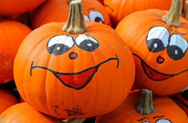 на ярких тыквах нарисованы смеющиеся лица