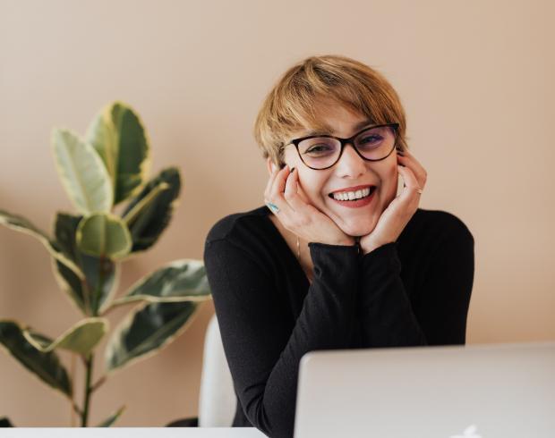 Девушка с короткими волосами в очках улыбается сидя за столом