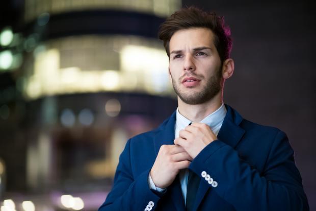 Молодой мужчина в костюме поправляет галстук