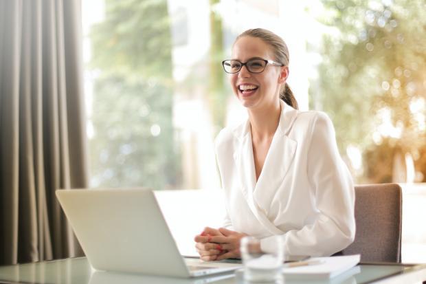 Девушка в белом смеется сидя за компьютером