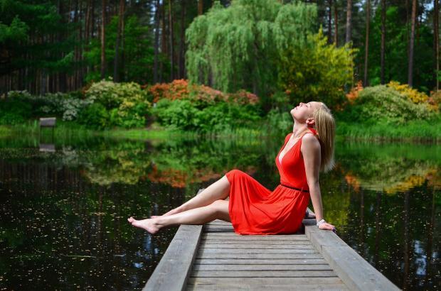 блондинка в красном платье сидит на пирсе у озера