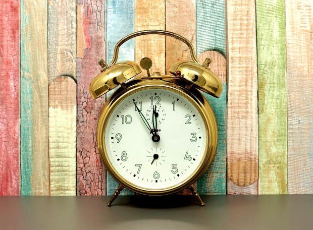 золотой будильник на фоне разноцветного забора