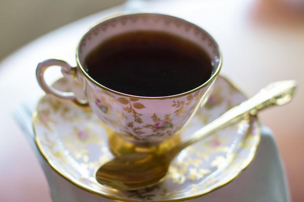 чашка с черным чаем на блюдце с ложечкой