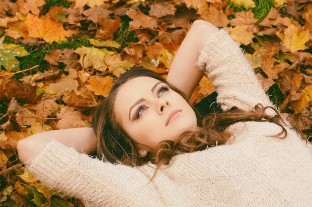 Девушка лежит на желтых листьях