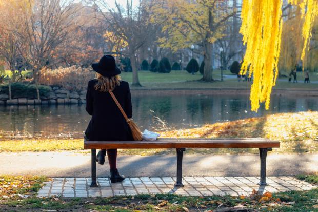 Девушка в черном сидит на лавке в осеннем парке