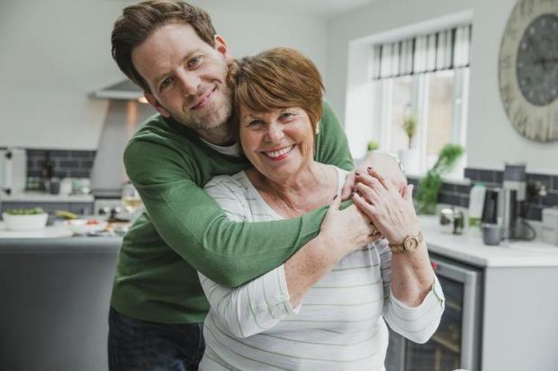 мама с сыном стоят улубваясь на кухне