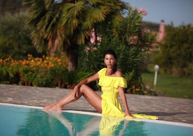 красивая девушка в желтом платье сидит на берегу моря
