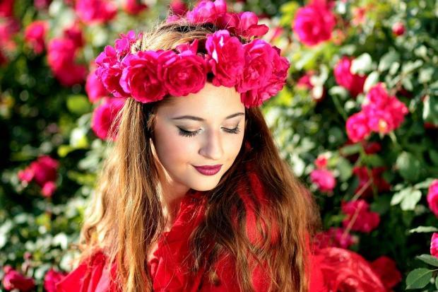 красивая девушка с венком из красных цветов на голове