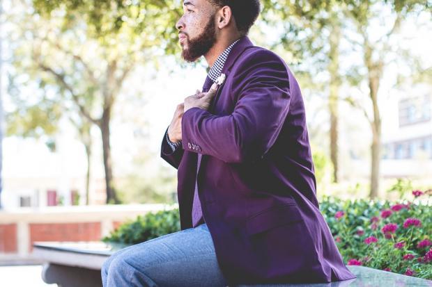 мужчина в фиолетовом пиджаке и синих джинсах сидит на скамейке