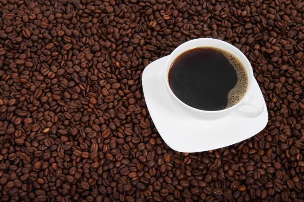 чашка с кофе стоит на кофейных зернах