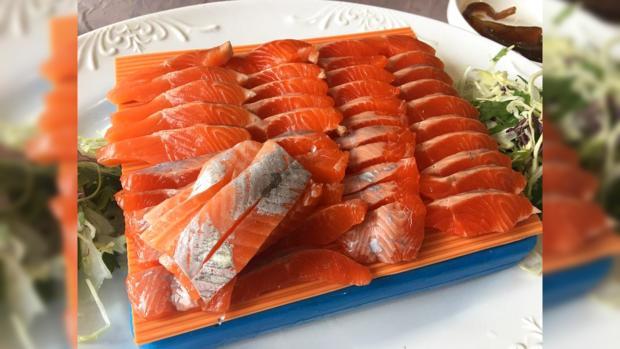 большое белое блюдо с нарезанными ломтиками лосося