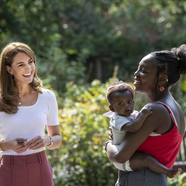 Кейт Миддлтон в белой футболке и розовых брюках общается с женщиной