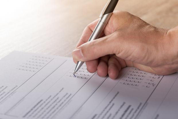 листик с тестом, человек ручкой отмечает ответы