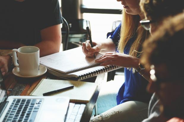 сидящие вокруг стола люди, ноутбук, блокнот, ручка
