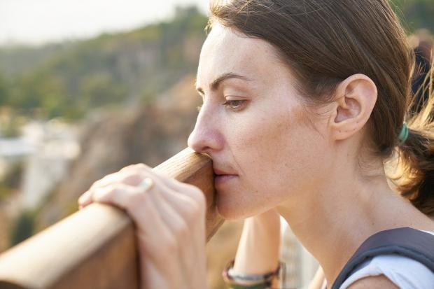 уткнувшаяся лицом в перила моста девушка грустно смотрит вдаль