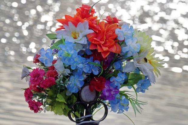 стоящие в вазе искусственные цветы различных оттенков