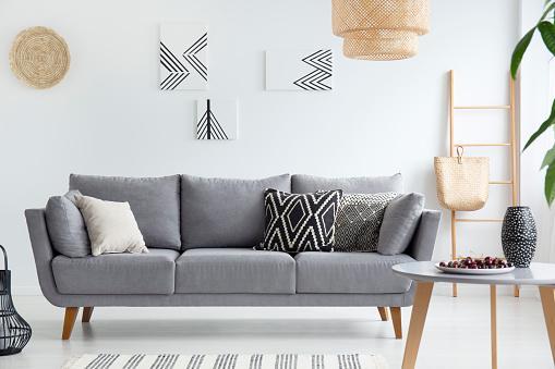 в светлой комнате стоит светлый диван с декоративными подушками