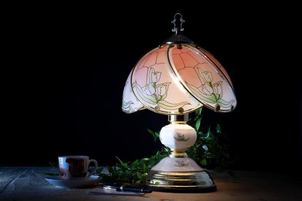 на столе стоит рядом с чашкой кофе красивая настольная лампа