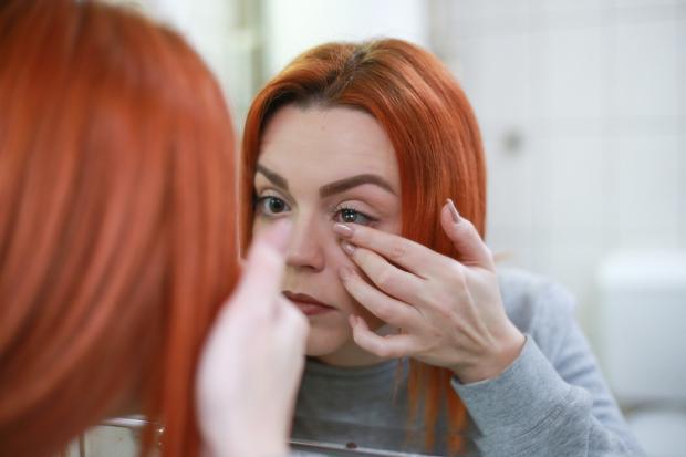 девушка перед зеркалом надевает контактную линзу