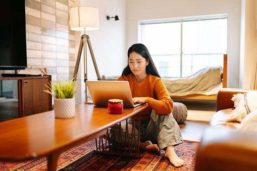 молодая японка сидит в комнате за ноутбуком