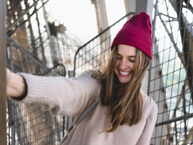 Девушка в розовом свитере и красной шапке улыбается
