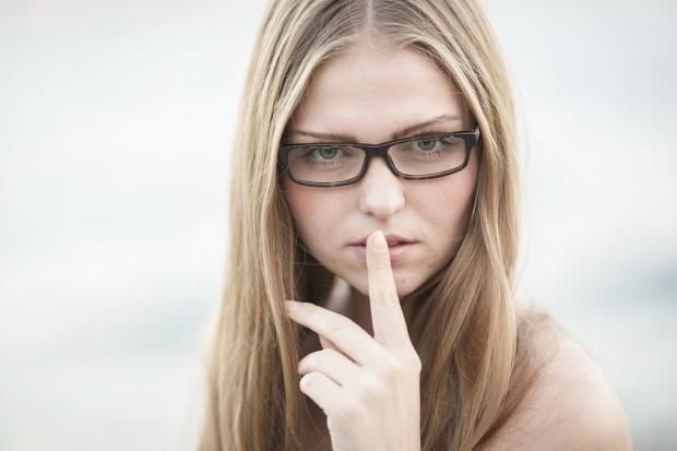 блондинка в очках держит палец у своих губ