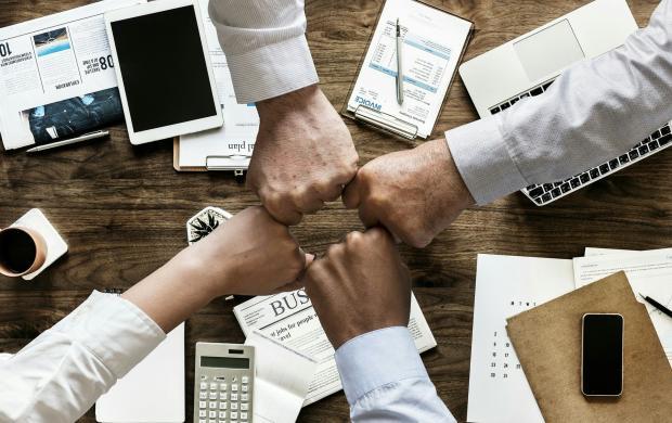 четыре мужские руки над офисным столом