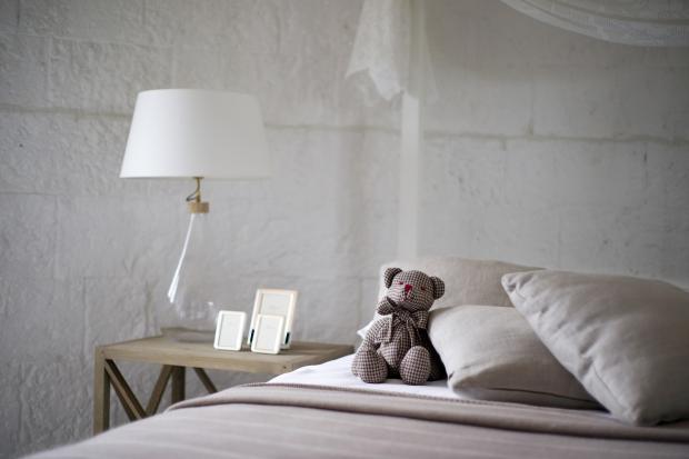на кровати сидит игрушечный медведь