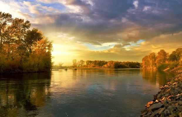 осенний пейзаж с гладью озера и низким небом с облаками