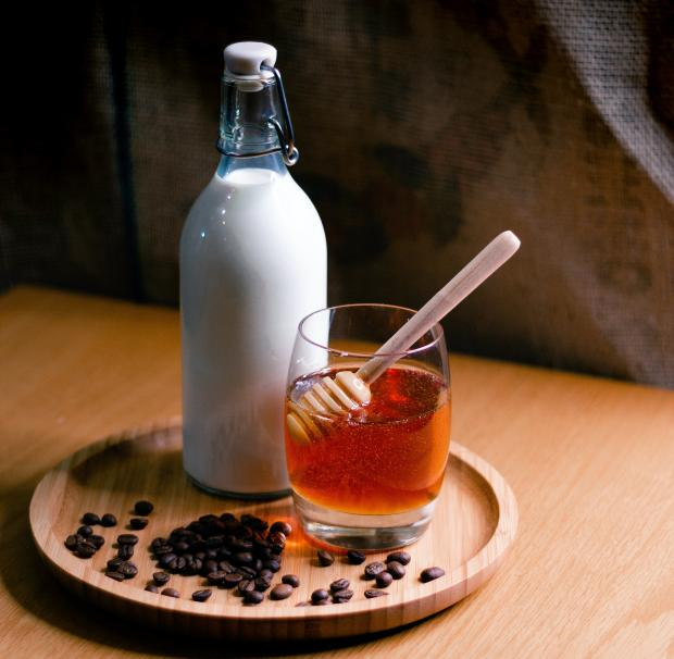 бутылка молока и банка с медом стоят на тарелке