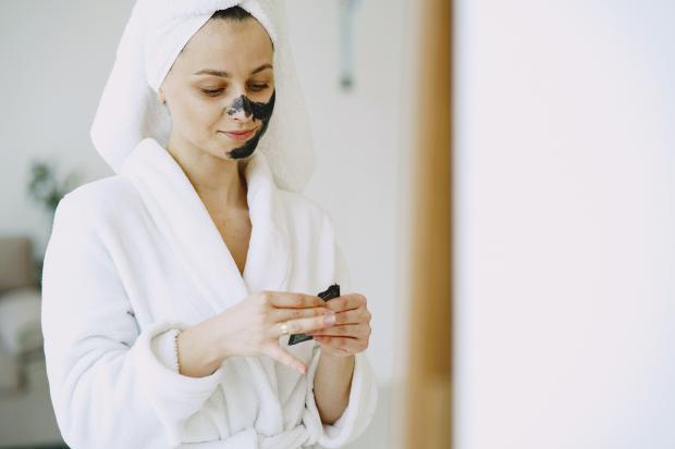 девушка в банном халате наносит скраб на лицо