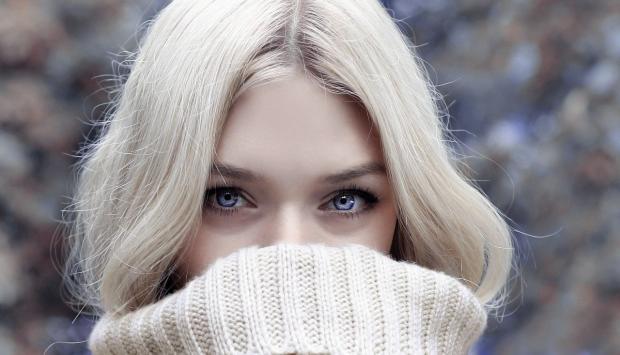 лицо красивой голубоглазой блондинки в белом свитере