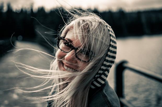 девушка в очках весело смеется
