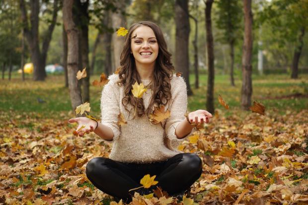 улыбающаяся девушка сидит на осенней листве