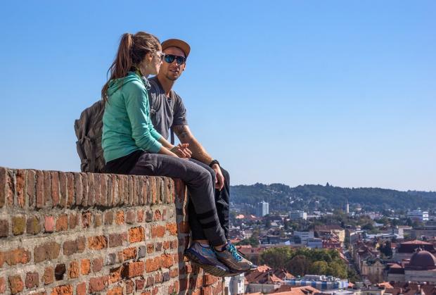 туристы сидят на кирпичной стене